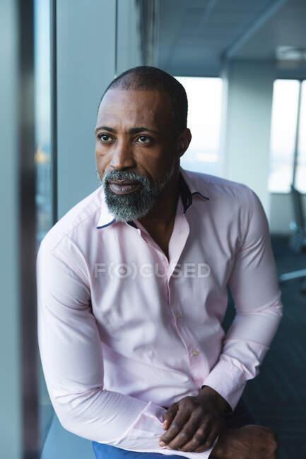 Афроамериканский бизнесмен, работающий допоздна в современном офисе, глядя в окно и думая:. — стоковое фото
