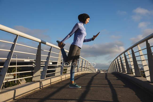 Convient aux femmes de race mixte portant du hijab et des vêtements de sport s'exerçant à l'extérieur de la ville par une journée ensoleillée, s'étirant pendant l'entraînement à l'aide d'un smartphone et d'écouteurs sur une passerelle. Exercice mode de vie urbain. — Photo de stock