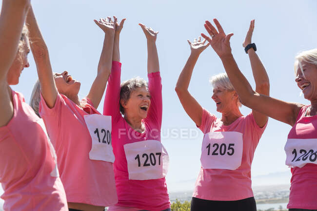 Group of Caucasian female friends enjoying exercising on a sunny day, smiling, celebrating after running race and wearing numbers. — стоковое фото