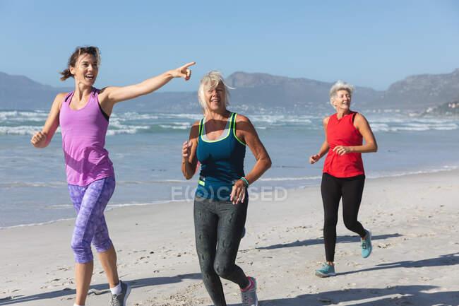 Группа кавказских подруг, занимающихся спортом на пляже в солнечный день, бегущих по берегу моря и улыбающихся. — стоковое фото