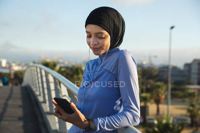 Convient aux femmes de race mixte portant du hijab et des vêtements de sport faisant de l'exercice à l'extérieur dans la ville par une journée ensoleillée, prenant une pause pendant l'entraînement à l'aide d'un smartphone et d'écouteurs sur une passerelle. Exercice mode de vie urbain. — Photo de stock