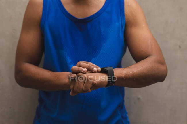 Mid section of man working out in an urban park, wearing sportswear taking a break checking smartwatch. Fitness strength healthy lifestyle. — стоковое фото