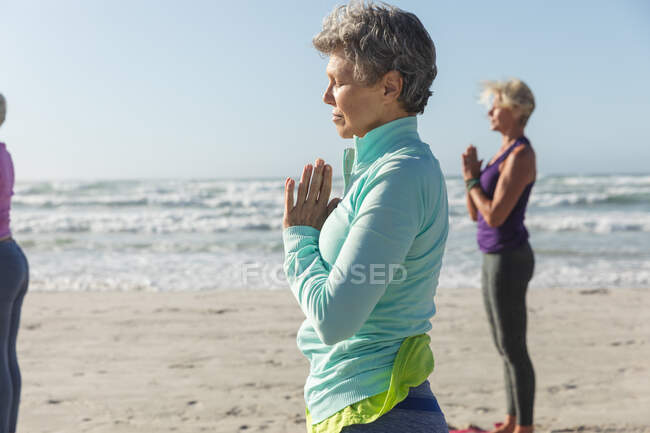 Group of Caucasian female friends enjoying exercising on a beach on a sunny day, practicing yoga and standing in yoga position. — Foto stock