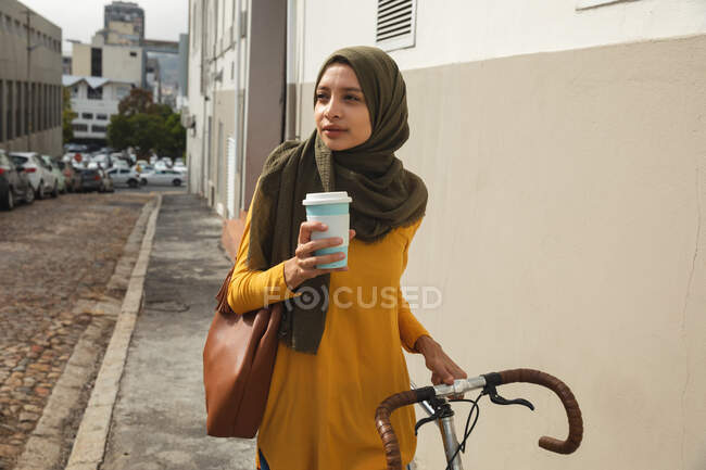 Mixed race woman wearing hijab and yellow jumper out and about on the go in the city, holding takeaway coffee walking with bike. Commuter modern lifestyle. — Stock Photo