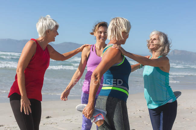Group of Caucasian female friends enjoying exercising on a beach on a sunny day, practicing yoga and stretching with sea in the background. — стоковое фото
