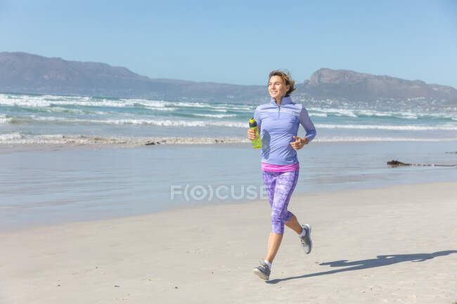 Caucasian woman enjoying exercising on a beach on a sunny day, running on the seashore, smiling and holding a bottle of water. — стоковое фото