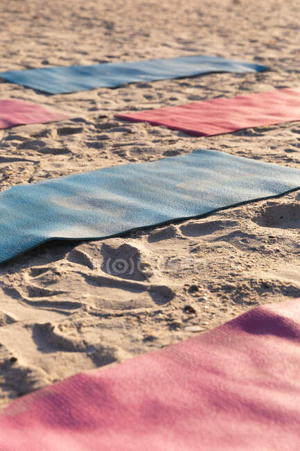 Close up of five colorful yoga mats on the beach by the sea on a sunny day. — Foto stock