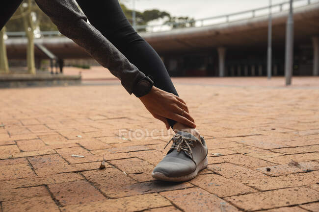 Fit woman wearing sportswear exercising outdoors in the city, warming up stretching in urban park. Urban lifestyle exercise. — стоковое фото
