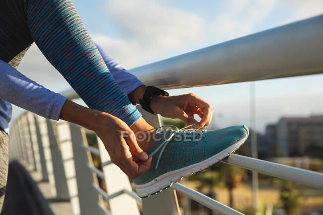 Partie médiane des vêtements de sport femme en forme exercice à l'extérieur dans la ville par une journée ensoleillée, prendre une pause pendant l'entraînement attacher lacets sur une passerelle. Exercice mode de vie urbain. — Photo de stock