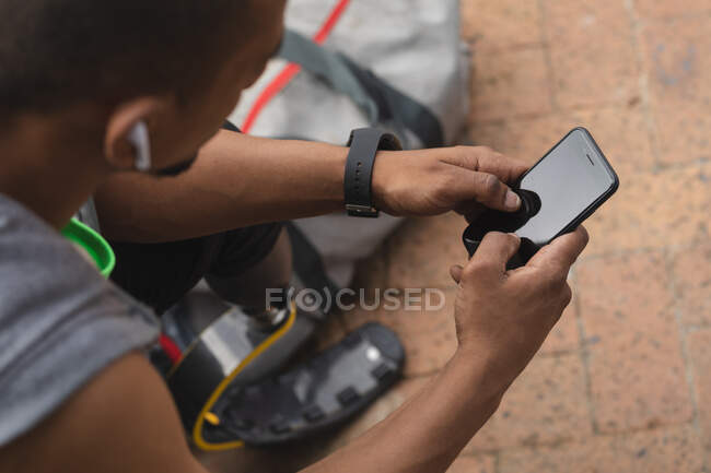 Disabled mixed race man with a prosthetic leg working out in an urban park, wearing wireless headphones taking a break, sitting and using smartphone. Fitness disability healthy lifestyle. — Foto stock