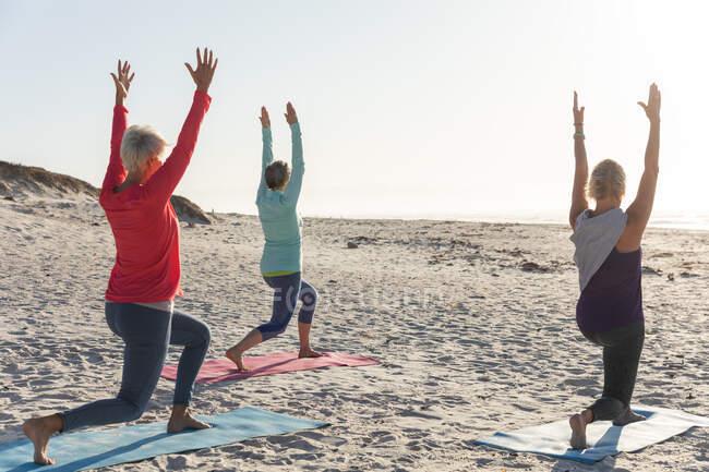 Группа кавказских подруг, занимающихся спортом на пляже в солнечный день, практикующих йогу и стоящих в позиции йоги. — стоковое фото