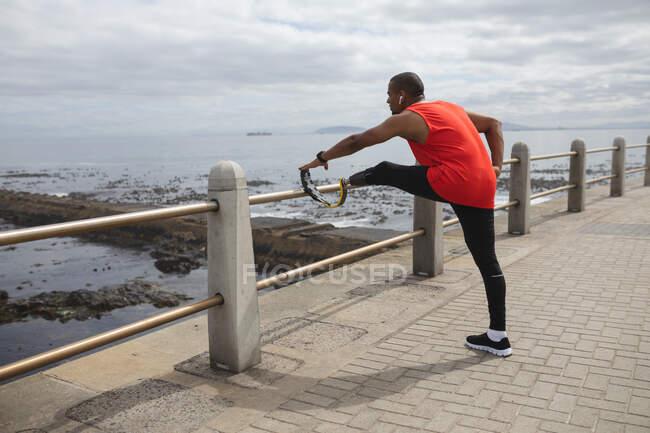 Инвалид смешанной расы с протезной ногой и бегущим лезвием, тренирующимся на побережье, в беспроводных наушниках, растягивая ноги с лезвием на заборе. Здоровый образ жизни. — стоковое фото