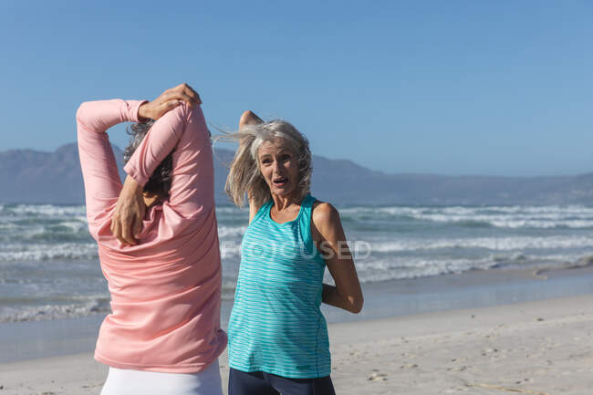 Two senior Caucasian female friends enjoying exercising on a beach on a sunny day, practicing yoga and stretching with sea in the background. — Stock Photo