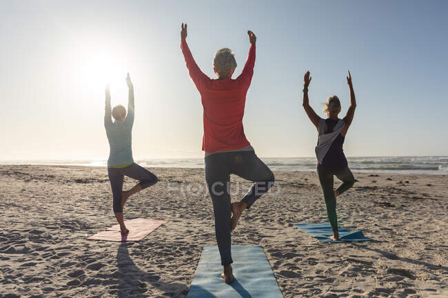 Group of Caucasian female friends enjoying exercising on a beach on a sunny day, practicing yoga, standing in tree position and facing the sea. — Stock Photo