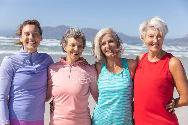 Portrait of a group of Caucasian female friends enjoying exercising on a beach on a sunny day, smiling, standing and looking at camera with sea in the background. — Fotografia de Stock