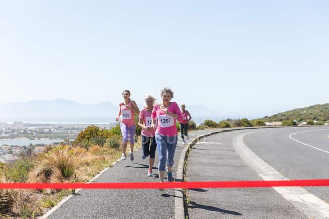Группа кавказских подруг, занимающихся спортом в солнечный день, бегущих по трассе и носящих номера, бегущих к финишу. — стоковое фото