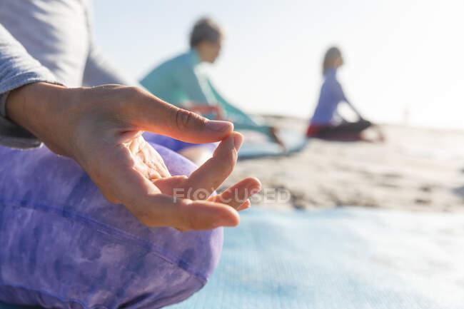 Primer plano de un grupo de amigas caucásicas disfrutando haciendo ejercicio en una playa en un día soleado, practicando yoga, meditando en posición de loto. - foto de stock