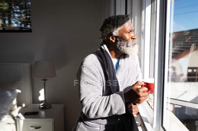 Afro-americano idoso em pé em um quarto, segurando uma xícara de café, olhando através de uma janela, distanciamento social e auto-isolamento em quarentena bloqueio — Fotografia de Stock