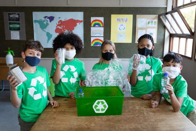 Портрет группы мультиэтнических детей в масках для лица, держащих пластиковые предметы в классе в школе. Начальное образование Социальное дистанцирование безопасности здоровья во время пандемии Coronavirus Covid19. — стоковое фото