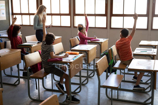 Group of multi ethnic kids sitting on their desk during the lesson with a female teacher wearing a face mask. Primary education social distancing health safety during Covid19 Coronavirus pandemic. — Stock Photo