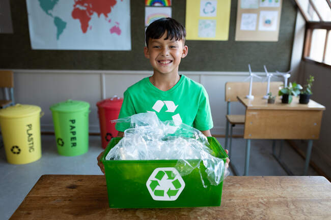 Portrait of a mixed race boy holding a recycle container in class at school. Primary education social distancing health safety during Covid19 Coronavirus pandemic. — Stock Photo