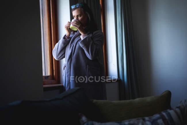 Кавказская женщина с длинными темными волосами наслаждается временем дома, социальным дистанцированием и самоизоляцией в карантинной изоляции, стоя, глядя в окно и держа чашку кофе. — стоковое фото