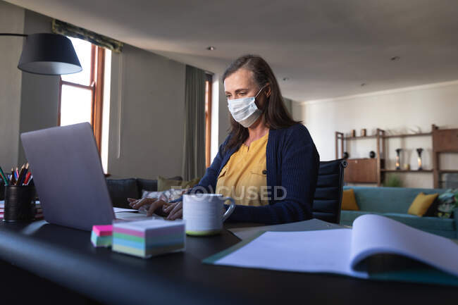Caucasian woman spending time at home, social distancing and self isolation in quarantine lockdown, sitting at table, using a laptop, wearing face mask protecting from Covid 19 coronavirus infection. — Stock Photo