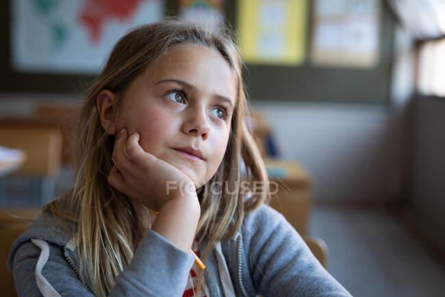 Une fille blanche réfléchie assise sur son bureau à l'école. Enseignement primaire distanciation sociale sécurité sanitaire pendant la pandémie de coronavirus Covid19. — Photo de stock