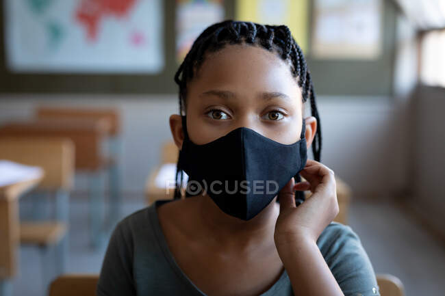 Portrait of a mixed race girl wearing a face mask, sitting on his desk in class at school. Primary education social distancing health safety during Covid19 Coronavirus pandemic. — Stock Photo