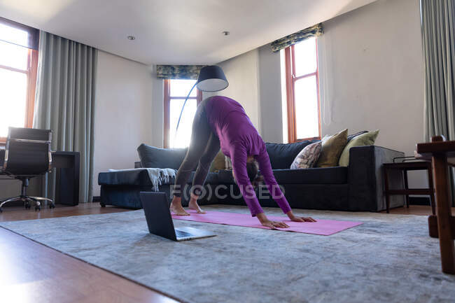 Caucasian woman enjoying time at home, social distancing and self isolation in quarantine lockdown, exercising in living room with laptop, practicing yoga, stretching. — Stock Photo
