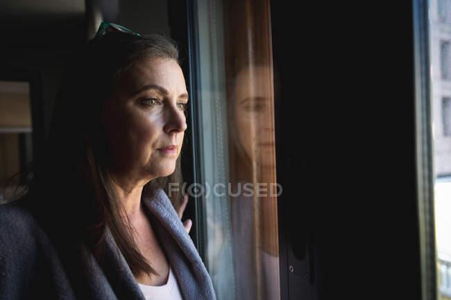 Mulher caucasiana com cabelos longos e escuros desfrutando do tempo em casa, distanciamento social e auto-isolamento em quarentena, de pé e olhando pela janela. — Fotografia de Stock