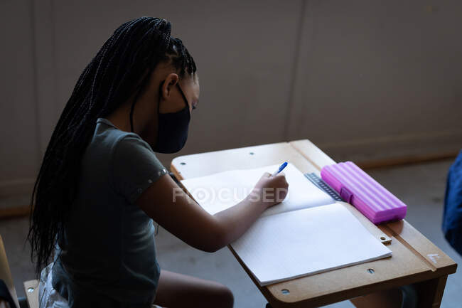 Mixed race girl wearing face mask writing while sitting on her desk at school. Primary education social distancing health safety during Covid19 Coronavirus pandemic. — Stock Photo