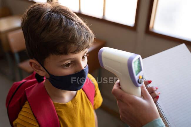 Кавказький хлопчик з масками обличчя вимірює температуру в початковій школі. Первинна освіта Соціальна безпека для здоров'я під час пандемії Ковіда19 Коронавірус. — стокове фото