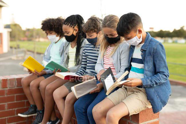 Группа этнических детей в масках для лица читает книги, сидя на стене во время перерыва. Начальное образование Социальное дистанцирование безопасности здоровья во время пандемии Coronavirus Covid19. — стоковое фото