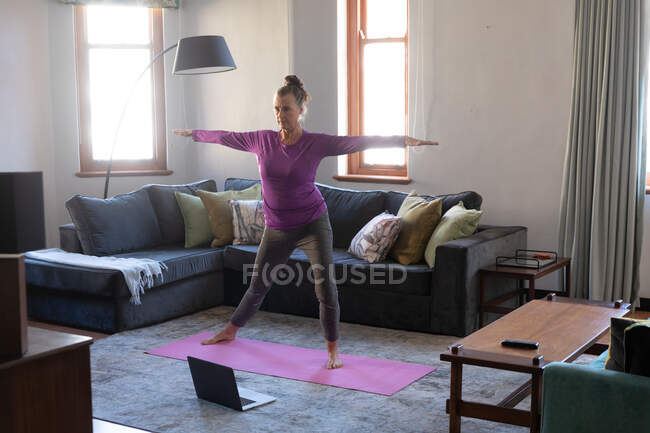 Caucasian woman enjoying time at home, social distancing and self isolation in quarantine lockdown, exercising in living room with laptop, stretching. — Stock Photo
