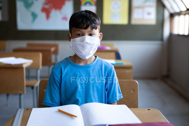 Mixed race boy wearing face mask sitting on his desk at school. Primary education social distancing health safety during Covid19 Coronavirus pandemic. — Stock Photo