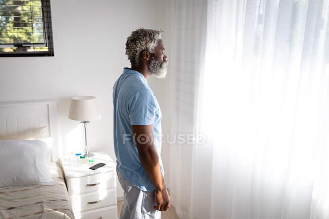 Homme âgé afro-américain debout dans une chambre à coucher, regardant par une fenêtre, distance sociale et isolement personnel en quarantaine verrouillé — Photo de stock