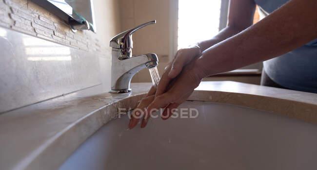 Corte médio da mulher em casa, distanciamento social e auto-isolamento em bloqueio de quarentena, lavar as mãos no banheiro protegendo de Covid 19 coronavírus. — Fotografia de Stock