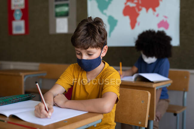 Two multi ethnic children sitting at desks wearing face masks in classroom. Primary education social distancing health safety during Covid19 Coronavirus pandemic. — Stock Photo