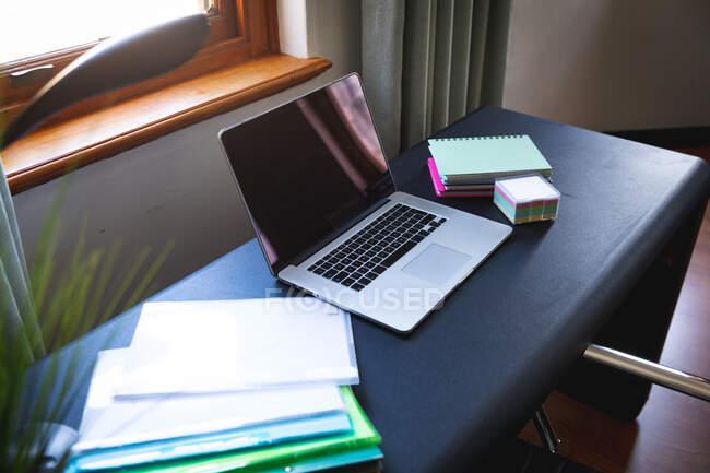 Общий вид домашнего офисного серого стола с ноутбуком, документами, файлами, блокнотами и записками, готового к работе из дома во время социального дистанцирования и самоизоляции в карантинной изоляции. — стоковое фото