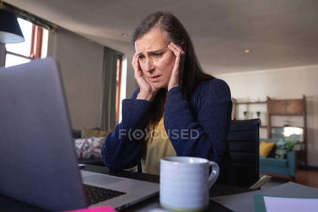 Worried Caucasian woman spending time at home, social distancing and self isolation in quarantine lockdown, sitting at table, using a laptop, massaging her temples. — Foto stock