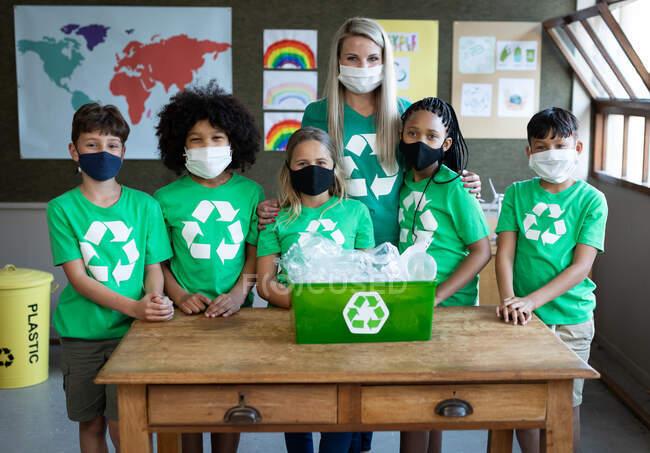Retrato de una maestra caucásica y un grupo de niños multiétnicos que usan máscaras faciales con contenedor de reciclaje en la escuela. Educación primaria distanciamiento social de la seguridad sanitaria durante el Covid19 Coronavirus. - foto de stock