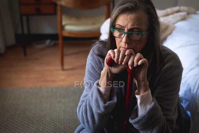 Mulher caucasiana preocupada passando tempo em casa, distanciamento social e auto-isolamento em quarentena, sentada no quarto, segurando a bengala. — Fotografia de Stock