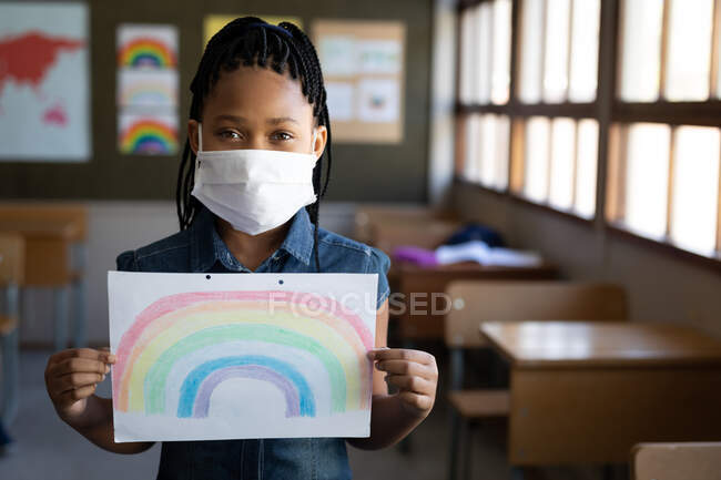 Portrait of a mixed race girl wearing face mask holding a rainbow drawing in the classroom. Primary education social distancing health safety during Covid19 Coronavirus pandemic. — Stock Photo