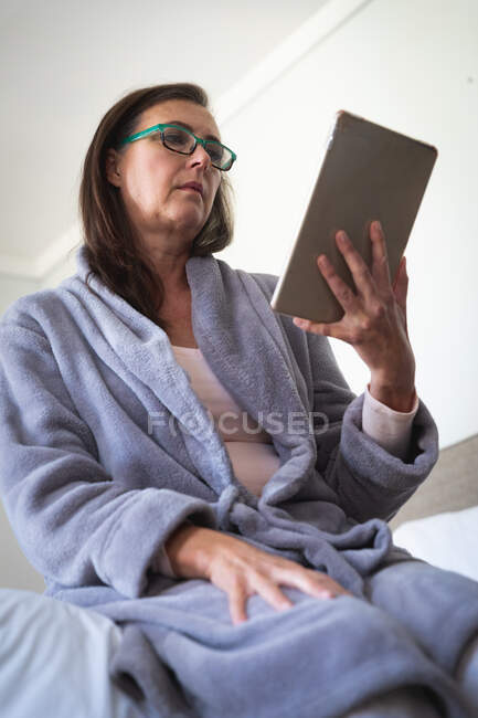 Mulher branca desfrutando de tempo em casa, distanciamento social e auto-isolamento em quarentena, sentada na cama no quarto, usando um tablet digital. — Fotografia de Stock