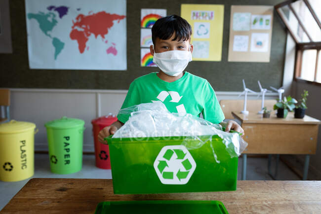 Portrait of a mixed race boy wearing face mask holding a recycle container in class at school. Primary education social distancing health safety during Covid19 Coronavirus pandemic. — Stock Photo