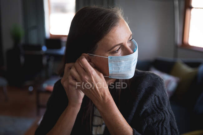 Caucasian woman enjoying time at home, social distancing and self isolation in quarantine lockdown, putting face mask on protecting from Covid 19 coronavirus infection. — Stock Photo