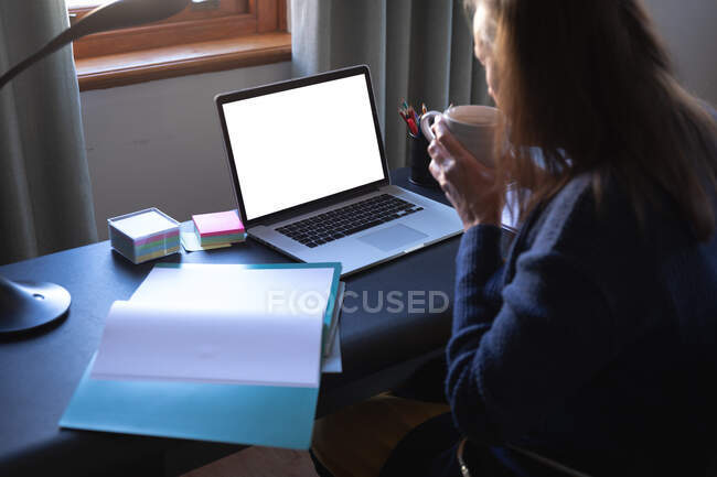 Caucasian woman enjoying time at home, social distancing and self isolation in quarantine lockdown, sitting at table, using a laptop, drinking coffee. — Foto stock