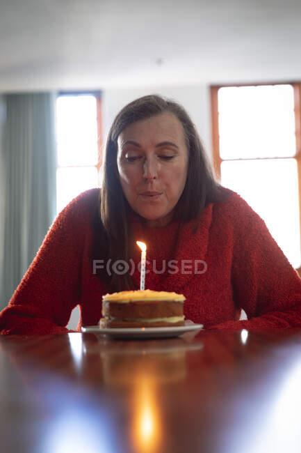 Mulher caucasiana feliz passar tempo em casa, distanciamento social e auto-isolamento em quarentena lockdown, sentado sozinho em uma mesa soprando vela no bolo de aniversário. — Fotografia de Stock