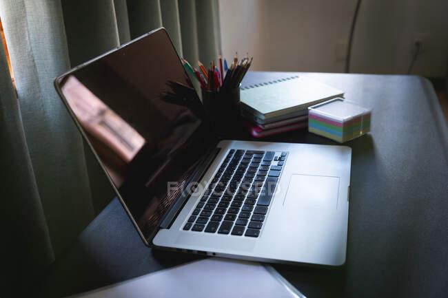 Общий вид домашнего офисного серого стола с ноутбуком, документами, карандашами, блокнотами, записками, готового к работе из дома во время социального дистанцирования и самоизоляции в карантинной изоляции. — стоковое фото